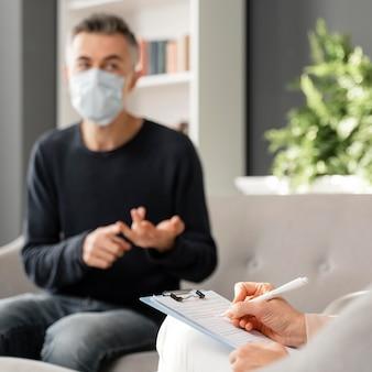 Tiro medio hombre preocupado con máscara hablando con consejera