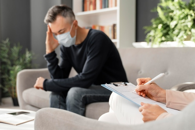 Tiro medio hombre preocupado con máscara en la oficina de terapia cerca del consejero