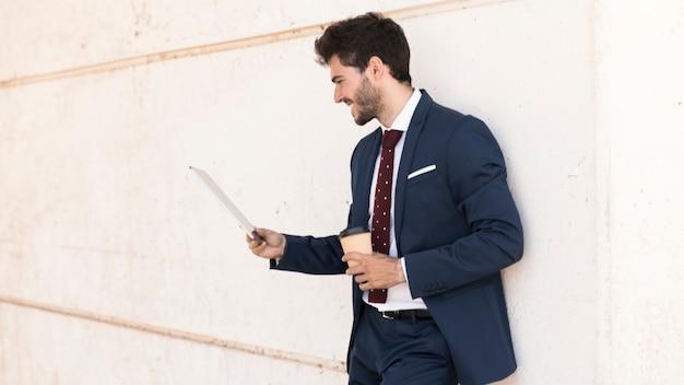 Tiro medio hombre sonriente con café y tableta