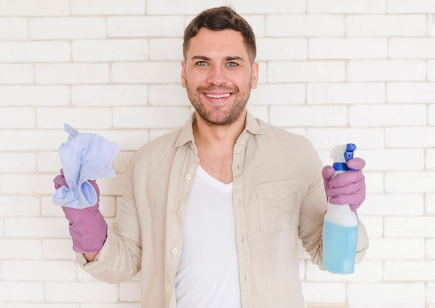 Tiro medio hombre sonriente con desinfectante