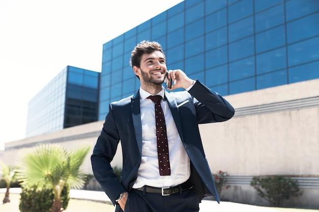 Tiro medio hombre sonriente hablando por teléfono