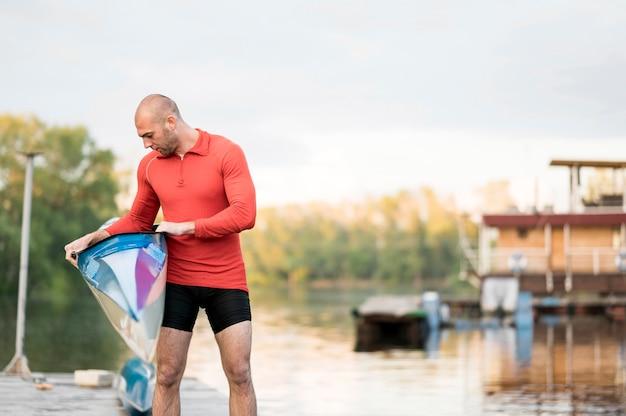 Tiro medio hombre sosteniendo kayak