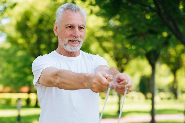 Tiro medio hombre sosteniendo saltar la cuerda