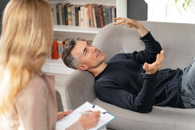 Tiro medio hombre tendido en el sofá en el gabinete de terapia