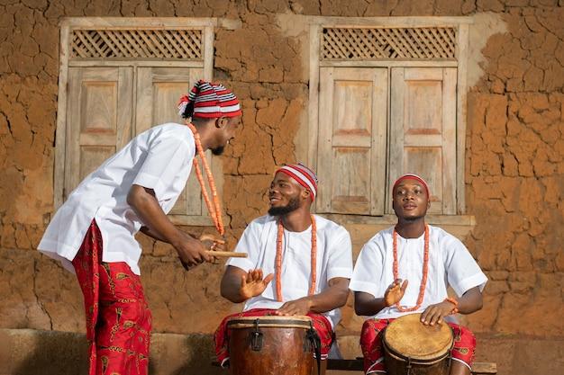 Tiro medio hombres nigerianos tocando música