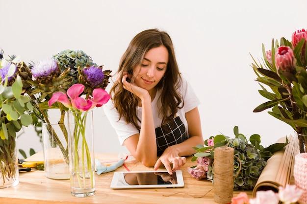 Tiro medio joven florista con tableta