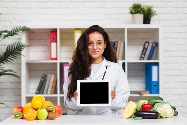 Tiro medio joven médico con maqueta de tableta