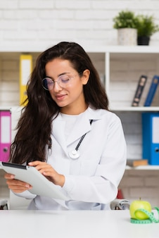 Tiro medio joven médico con tableta