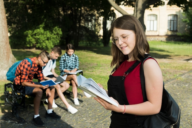 Tiro medio lateral de una chica highshool leyendo un libro