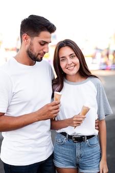 Tiro medio linda pareja comiendo un helado