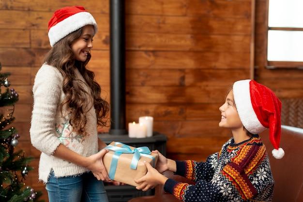 Tiro medio lindo hermano y hermana compartiendo regalo