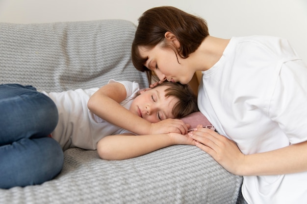 Tiro medio madre besando a niña en la cabeza.