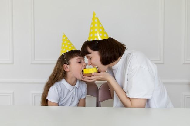 Tiro medio madre y niña comiendo cupcake