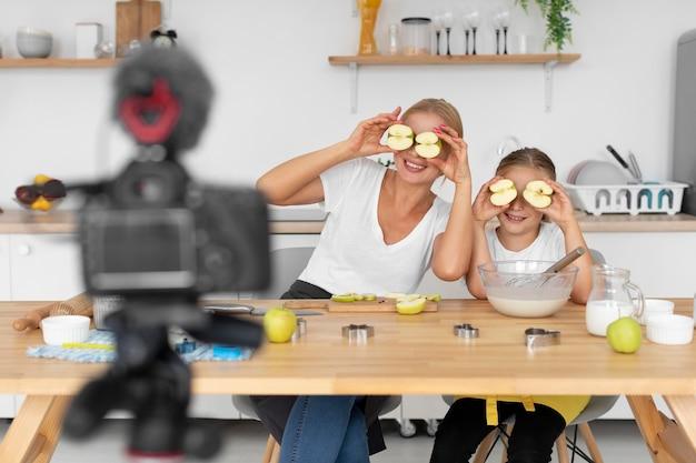 Tiro medio madre y niña sosteniendo manzanas