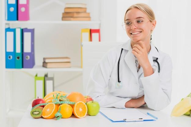 Tiro medio médico sonriente con frutas saludables