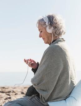 Tiro medio mujer con auriculares al aire libre