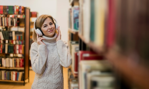 Tiro medio mujer con auriculares cerca de estantería