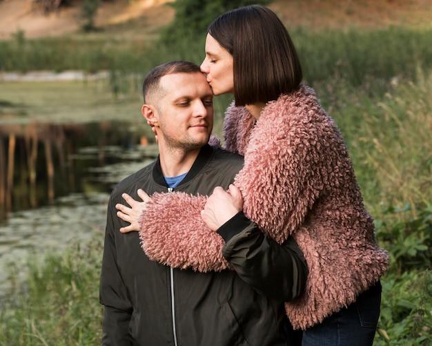 Tiro medio mujer besando a novio