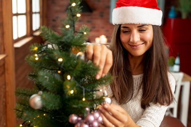 Tiro medio mujer feliz decorando el árbol de navidad