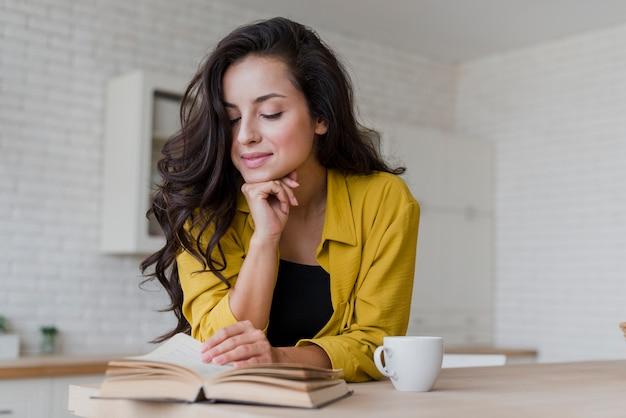 Tiro medio mujer feliz leyendo en la cocina