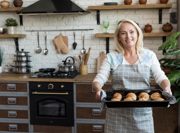 Tiro medio mujer feliz llevando bandeja con croissants