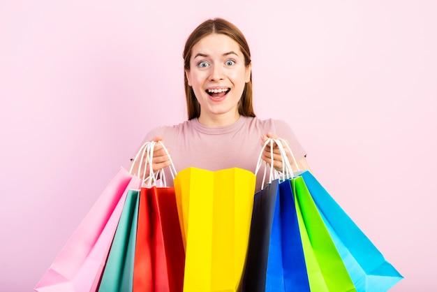 Tiro medio mujer feliz sosteniendo bolsas y mirando a cámara