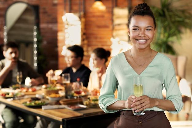 Tiro medio mujer feliz sosteniendo un vaso