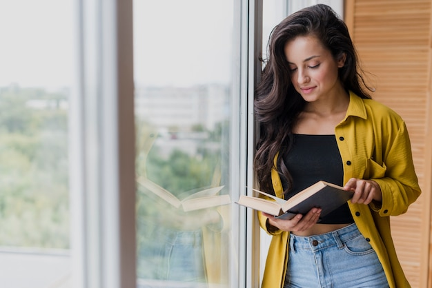 Tiro medio mujer leyendo cerca de la ventana