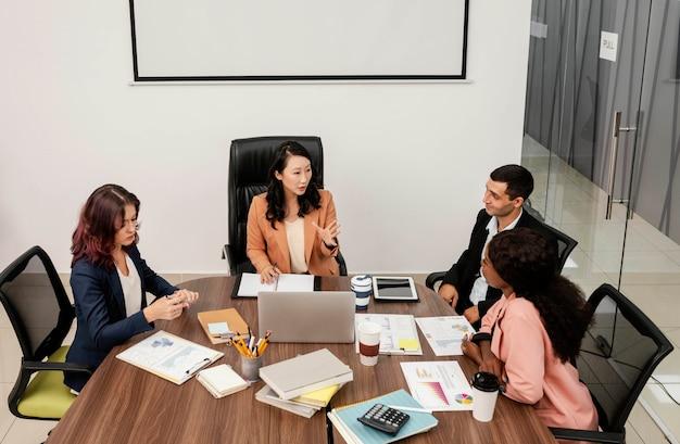Tiro medio mujer líder del equipo en el escritorio