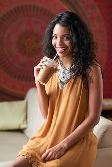 Tiro medio de mujer morena disfrutando de su café helado sentado en el sofá