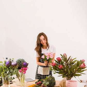Tiro medio mujer que trabaja en la tienda de flores