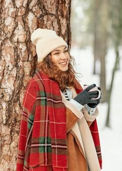 Tiro medio mujer recostada sobre el árbol