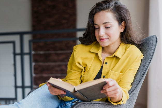 Tiro medio mujer sentada y leyendo