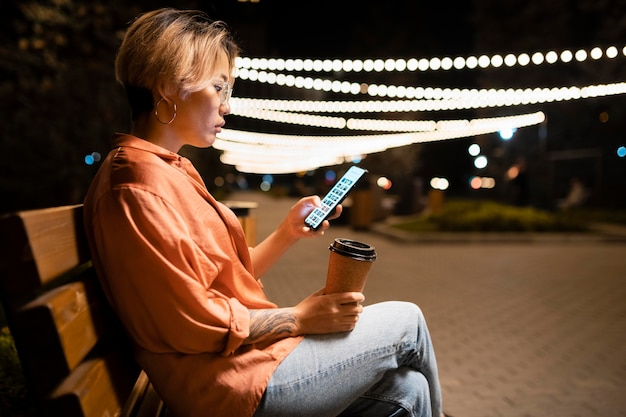 Tiro medio mujer sentada con teléfono