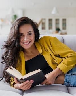 Tiro medio mujer sonriente con libro