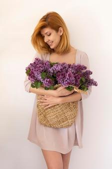 Tiro medio mujer sonriente sosteniendo canasta de flores