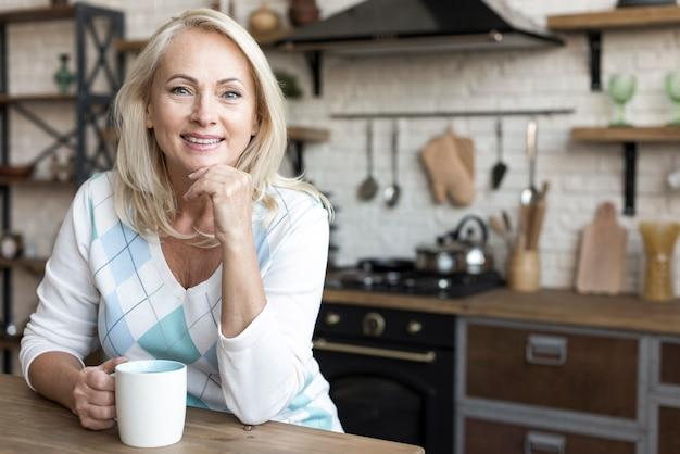 Tiro medio mujer sonriente sosteniendo una taza