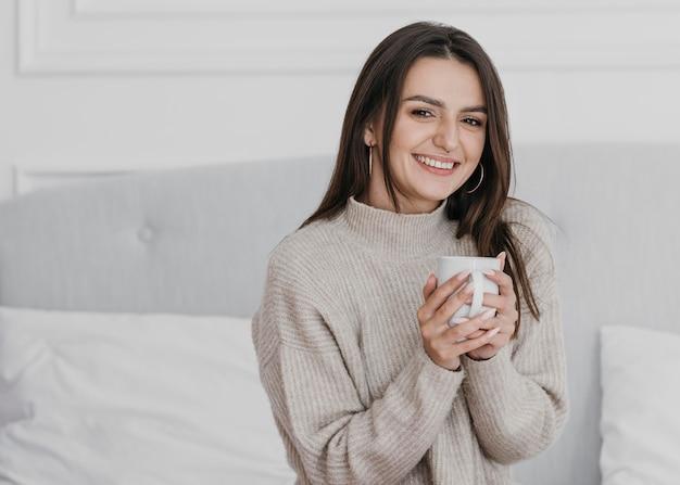 Tiro medio mujer sonriente sosteniendo la taza