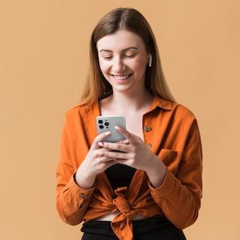 Tiro medio mujer sonriente sosteniendo teléfono