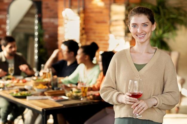 Tiro medio mujer sonriente sosteniendo un vaso
