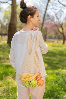 Tiro medio mujer sosteniendo una bolsa reutilizable con comida en la naturaleza