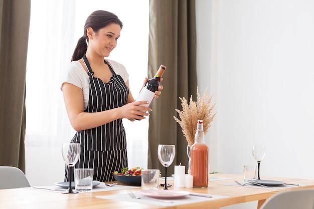 Tiro medio mujer sosteniendo una botella de vino