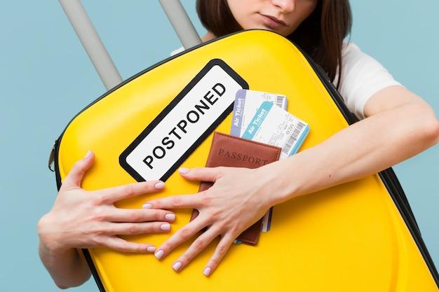 Tiro medio mujer sosteniendo un equipaje amarillo con un cartel pospuesto