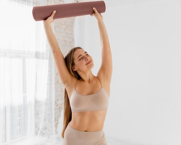 Tiro medio mujer sosteniendo estera de yoga