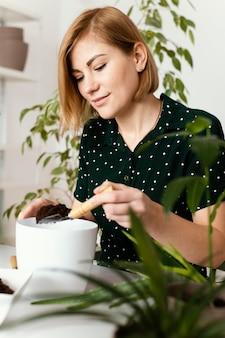 Tiro medio mujer sosteniendo paleta de jardinería