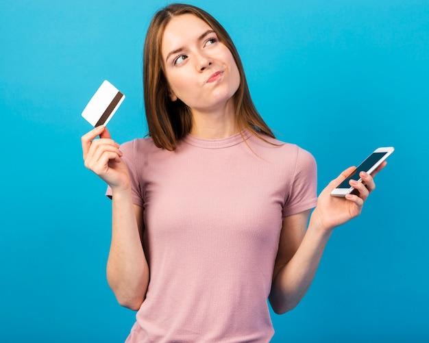 Tiro medio mujer sosteniendo tarjeta de crédito y teléfono y mirando a otro lado