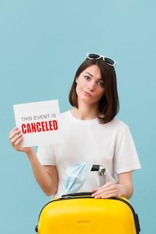 Tiro medio mujer sosteniendo una tarjeta con un mensaje de evento cancelado