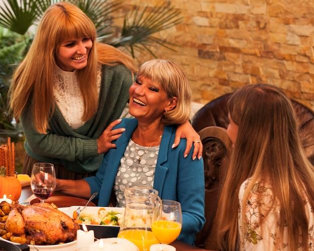 Tiro medio mujeres felices en la mesa de la cena