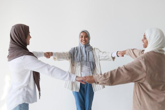 Tiro medio mujeres musulmanas cogidos de la mano