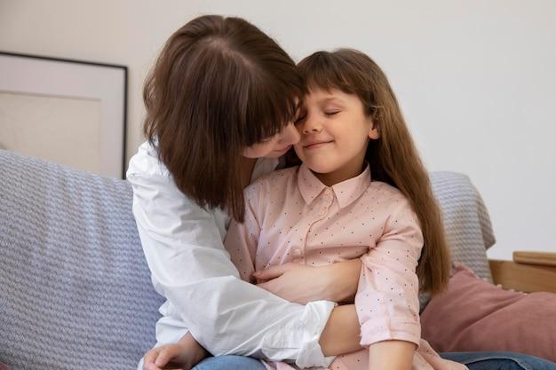 Tiro medio niña y madre en el sofá